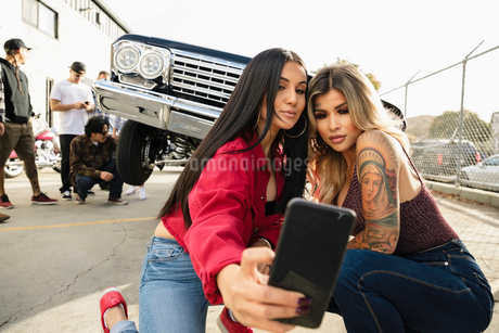 Latinx young women taking selfie in front of low rider on urban streetの写真素材 [FYI02335811]