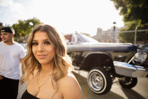Portrait confident Latinx young woman in front of low rider car in parking lotの写真素材 [FYI02335844]