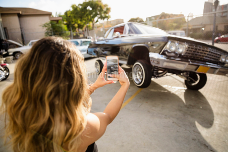 Latinx young woman with camera phone photographing low rider car bouncing in sunny parking lotの写真素材 [FYI02335862]