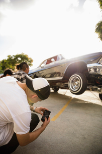 Latinx young man with camera phone photographing low rider car bouncing in parking lotの写真素材 [FYI02335871]