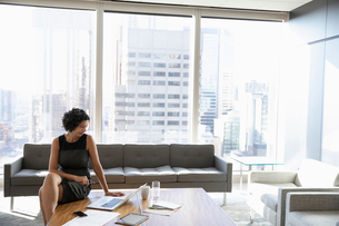 Businesswoman working at laptop in urban office loungeの写真素材 [FYI02335887]
