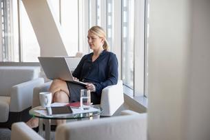 Businesswoman using laptop in office loungeの写真素材 [FYI02335897]