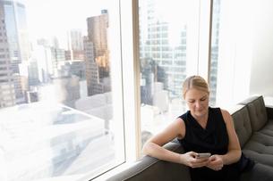 Businesswoman using smart phone in urban office windowの写真素材 [FYI02335898]