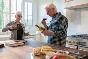 Senior couple drinking wine in kitchenの写真素材 [FYI02335899]