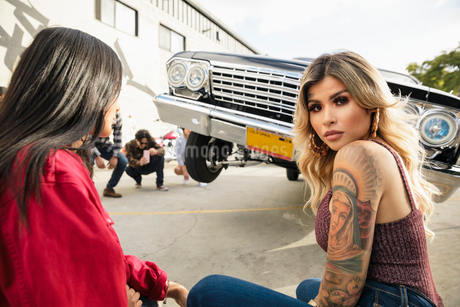 Portrait confident Latinx young woman with tattoos in front of low rider car bouncing in parking lotの写真素材 [FYI02335947]