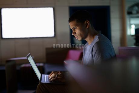 Dedicated businessman working late at laptop in dark officeの写真素材 [FYI02335981]
