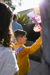 Latinx boy waving American flag on sidewalkの写真素材 [FYI02335985]