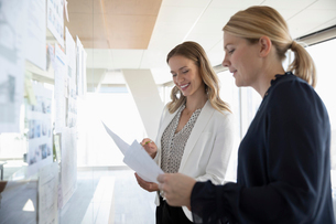 Female architects reviewing blueprints in office meetingの写真素材 [FYI02335988]