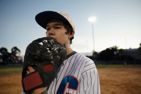 Determined Latinx baseball player on field at nightの写真素材 [FYI02335990]