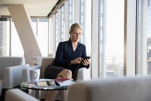 Businesswoman using smart phone in office loungeの写真素材 [FYI02336003]