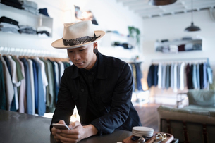 Male business owner using smart phone in menswear clothing shopの写真素材 [FYI02336012]