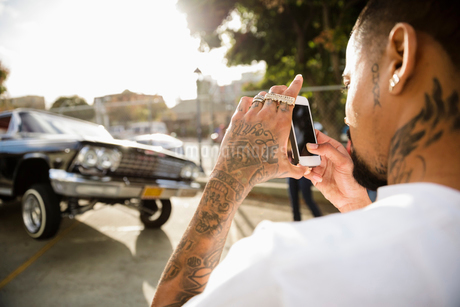 Latinx man with tattoos photographing low rider car bouncing in parking lotの写真素材 [FYI02336041]