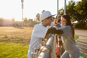 Baseball player talking to girlfriend at sunny fenceの写真素材 [FYI02336051]