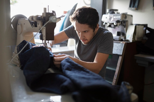 Focused male tailor using sewing machine in denim repair shopの写真素材 [FYI02336094]