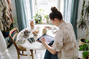 Female artist sketching on digital tablet at tableの写真素材 [FYI02336097]