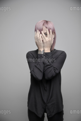 Portrait beautiful non-binary gender person with pink hair hiding behind handsの写真素材 [FYI02336108]