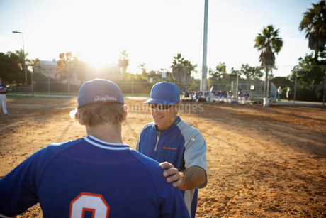 Coach talking with baseball player on sunny fieldの写真素材 [FYI02336117]