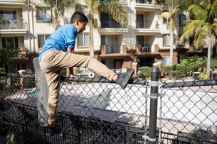 Boy jumping apartment swimming pool fenceの写真素材 [FYI02336119]