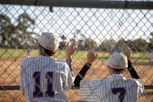 Baseball players watching game from behind fenceの写真素材 [FYI02336120]