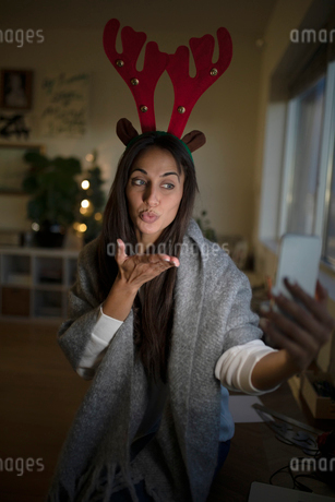 Young woman in Christmas antlers taking selfie and blowing a kissの写真素材 [FYI02336122]