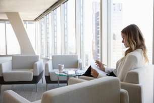 Businesswoman reviewing paperwork in office loungeの写真素材 [FYI02336130]