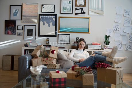 Portrait young woman surrounded by Christmas gifts in living roomの写真素材 [FYI02336162]