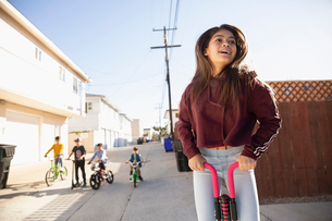 Latinx tween girl playing with pogo stick in alleyの写真素材 [FYI02336180]