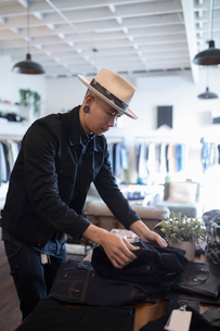 Male business owner arranging display in menswear clothing shopの写真素材 [FYI02336207]