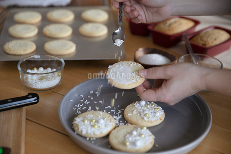 Woman decorating Christmas cookies with sprinklesの写真素材 [FYI02336308]