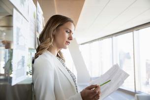 Focused businesswoman reviewing paperwork in officeの写真素材 [FYI02336318]