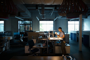 Dedicated businessman working late at computer, drinking coffee at sit-stand desk in dark officeの写真素材 [FYI02336338]