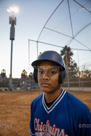Portrait confident, determined baseball player on field at nightの写真素材 [FYI02336395]