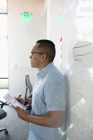 Businessman with digital tablet leading conference room meeting at whiteboardの写真素材 [FYI02336396]
