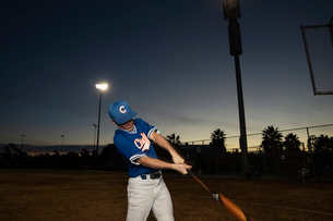 Baseball player with bat practicing swing on field at nightの写真素材 [FYI02336429]