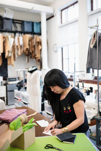 Female fashion designer working in studioの写真素材 [FYI02336495]