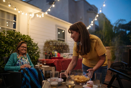 Latinx daughter and senior mother cleaning up after barbecue on patioの写真素材 [FYI02336507]