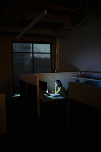 Dedicated businesswoman working late at computer in dark office cubicleの写真素材 [FYI02336549]