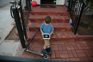 Latinx boy with scooter using digital tablet on front stoopの写真素材 [FYI02336563]