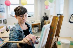 Focused female artist painting in studioの写真素材 [FYI02336577]
