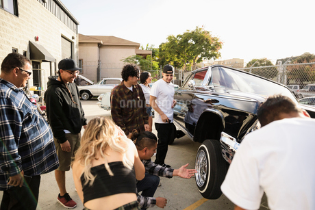 Latinx friends checking out low rider car in parking lotの写真素材 [FYI02336631]