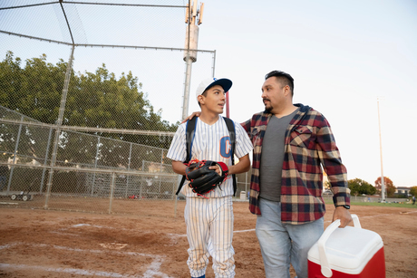 Latinx father and baseball player son walking off fieldの写真素材 [FYI02336658]