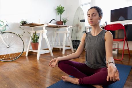 Serene young Latinx woman meditating on yoga matの写真素材 [FYI02336659]