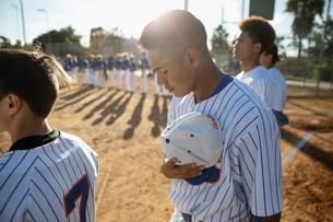 Reverent baseball player removing hat for national anthem on sunny fieldの写真素材 [FYI02336663]