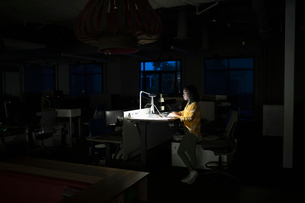 Businesswoman working late at sit-stand desk in dark officeの写真素材 [FYI02336679]