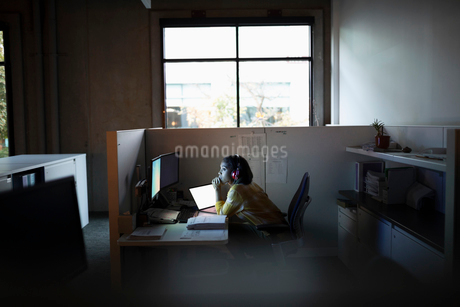 Dedicated businesswoman working late at computer in office cubicleの写真素材 [FYI02336699]