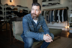 Confident male business owner sitting in menswear clothing shopの写真素材 [FYI02336706]