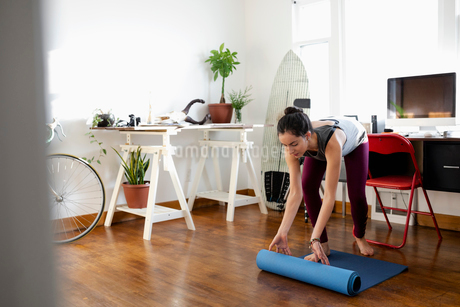 Young Latinx woman unrolling yoga mat in apartmentの写真素材 [FYI02336755]