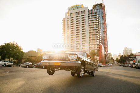 Low rider car bouncing on sunny urban streetの写真素材 [FYI02336764]