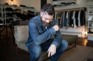 Smiling man with beard in menswear clothing shopの写真素材 [FYI02336775]