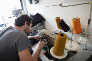 Focused male tailor working at sewing machine in denim repair shopの写真素材 [FYI02336888]